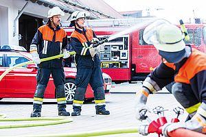 Das Bild zeigt Feuerwehrmänner bei einem Löscheinsatz und verdeutlicht die Bedeutung von Feuerwehrgebühren.