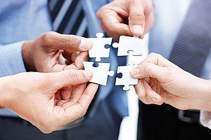 Das Bild zeigt vier Personen, die jeweils ein passendes Puzzleteil zu einem quadratischen Ganzen zusammenführen.