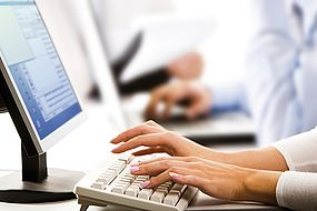 Das Bild zeigt einen Mitarbeiter, der einen Computer bedient, u.a. um eine Stelle zu bewerten.