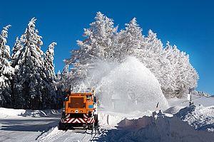 Das Bild zeigt wie ein Fahrzeug des Winterdienstes die Straßenreinigung vornimmt.