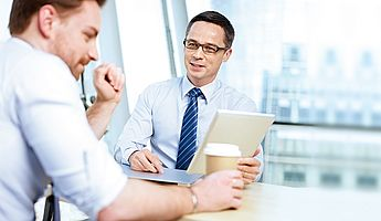 Das Bild zeigt wie ein Berater mit einem Kunden gemeinsam einen Geschäftsprozess optimiert.