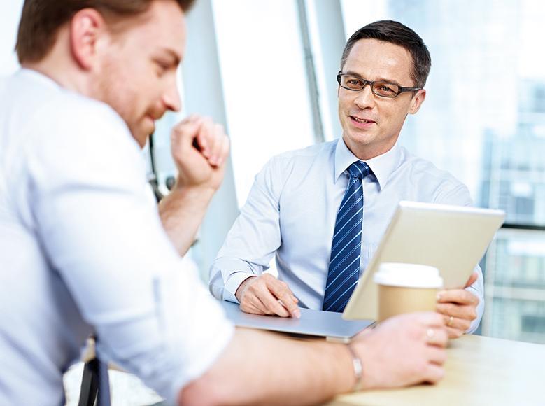Das Bild zeigt zwei Kollegen, die sich am PC zu einem Projekt austauschen.