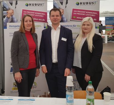 Auf diese Bild sind drei Mitarbeiter am Stand der KUBUS auf der 11. StuWi-Firmenkontaktbörse an der Hochschule Wismar zu sehen.